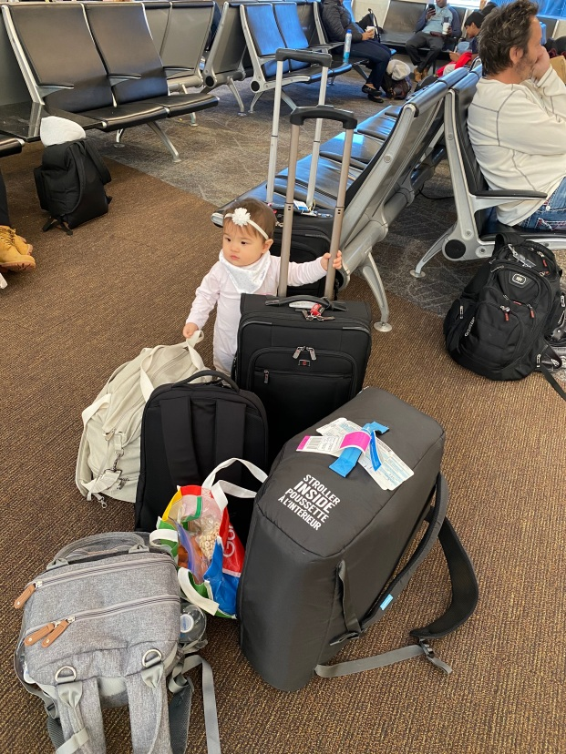 Baby standing in the airport holding onto many pieces of luggage