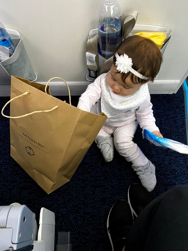 Baby playing with a gift bag on the floor of an airplane
