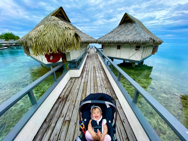 Baby laughing near an overwater bungalows in Moorea, French Polynesia