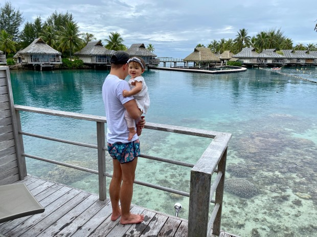 Dad and baby looking at clear ocean water in Moorea, French Polynesia