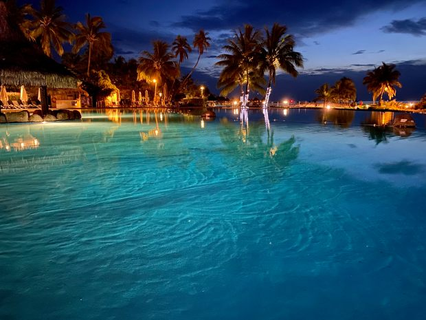 Intercontinental pool in Tahiti at dusk with palm trees and turquoise water