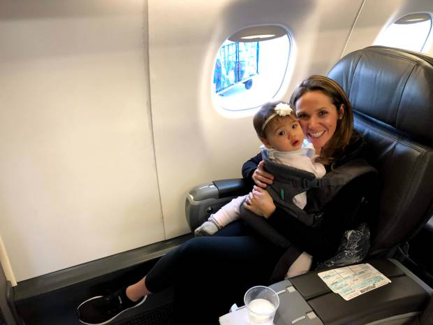 Mom and baby sitting in first class airplane seat