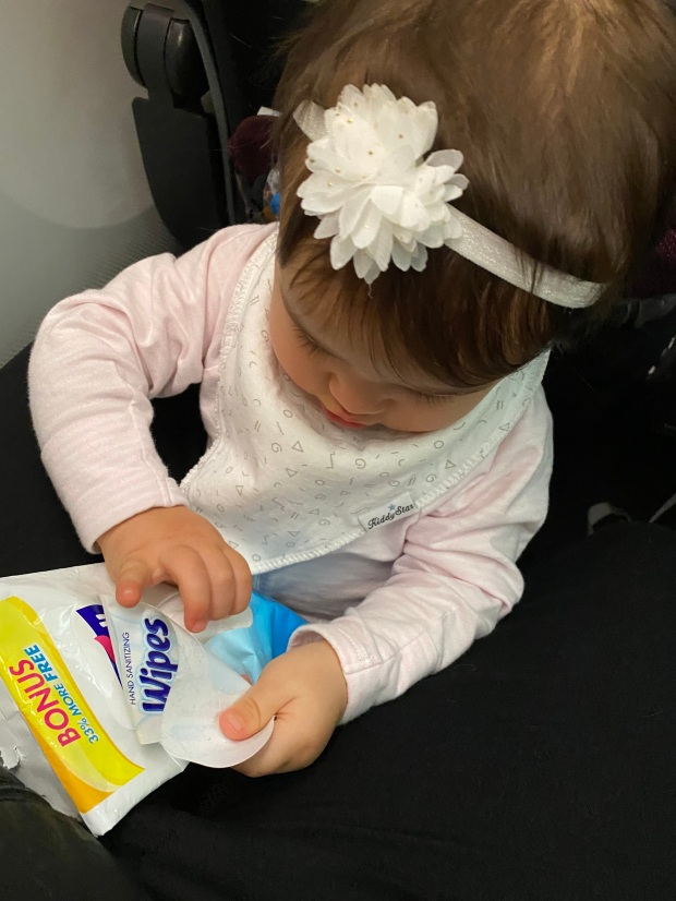 Baby using sanitizing wipes on an airplane