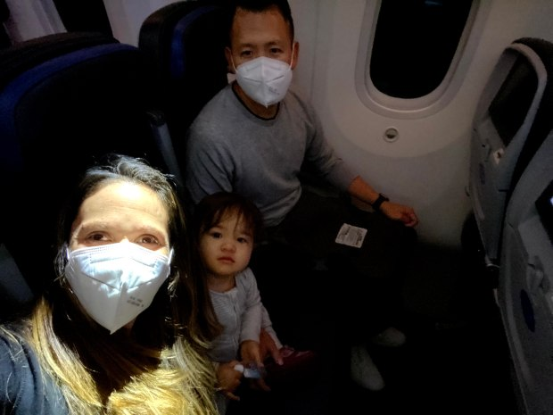 Two parents and a toddler flying with face masks