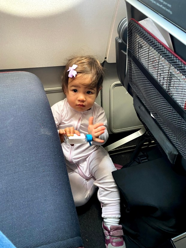 Baby on the floor of an airplane with sanitizer bottle